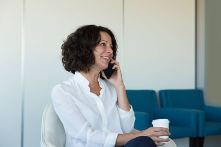 Happy businesswomen talking on cell while drinking coffee. Business woman sitting in office corridor, speaking on cellphone and laughing. Phone talk concept