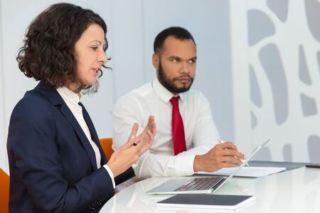Serious business people explaining project details at meeting. Business man and woman with laptop and papers sitting at conference table and speaking. Business meeting concept