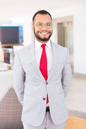 Cheerful handsome businessman posing in office hallway. Happy business man in office suit and tie standing for camera and smiling. Confident businessman portrait concept