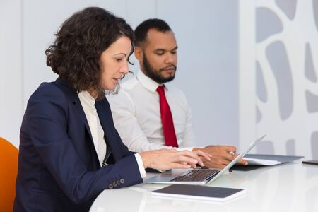 Serious business colleagues checking computer and documents during meeting. Business man and woman sitting at conference table, using laptop, reading papers. Business seminar concept Stock Photo