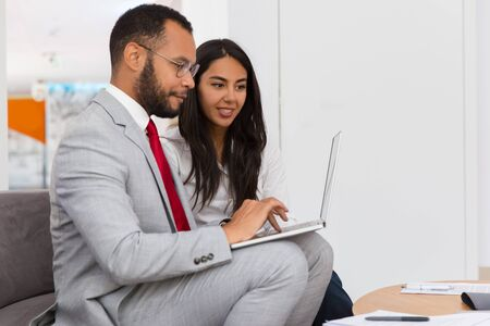Excited colleagues watching project presentation in rest room. Business man and woman sitting on office couch, using laptop, looking at screen. Networking concept