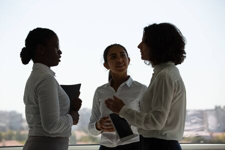 Excited colleagues discussing project near office window. Three businesswomen standing together and talking. Team discussion concept Stock Photo