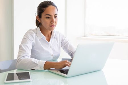 Serious female office employee working on computer. Young Latin businesswoman sitting at workplace, using laptop, typing, looking at screen. White office interior concept