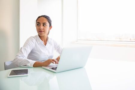 Confident female consultant working on computer. Young Latin businesswoman sitting at workplace, using laptop, looking away. Professional at workplace concept