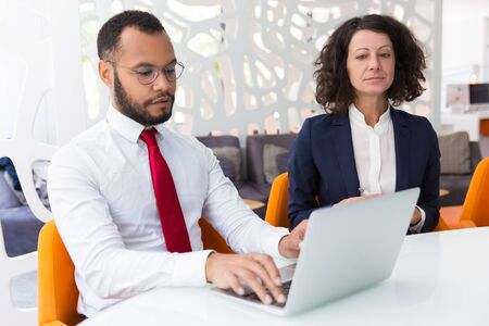 Businessman using computer during conference. Business man typing on laptop, his colleague looking at screen. Business conference concept Stock Photo