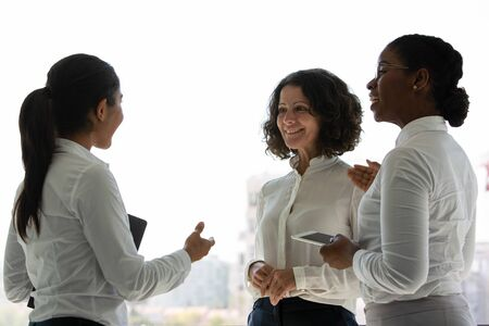 Team of happy female colleagues chatting near office window. Businesswomen standing together, talking, gesturing and smiling. Business networking concept