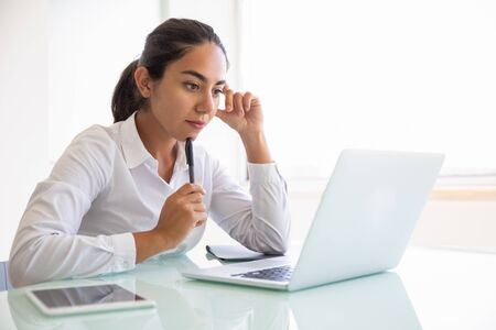 Serious pensive businesswoman watching content on computer. Young Latin business woman sitting at workplace, using laptop, looking at screen. Digital communication concept