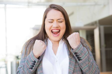 Successful young woman with raised fists. Happy cheering lady with closed eyes. Concept of success