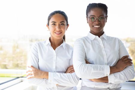 Happy female business colleagues posing together near office window. Two diverse businesswomen standing for camera with arms folded and smiling. Diverse team concept