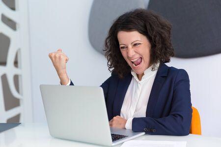 Feliz empresaria emocionada haciendo gesto de ganador. Mujer de negocios usando la computadora, mirando la pantalla y gritando de alegría. Buenas noticias o concepto de éxito