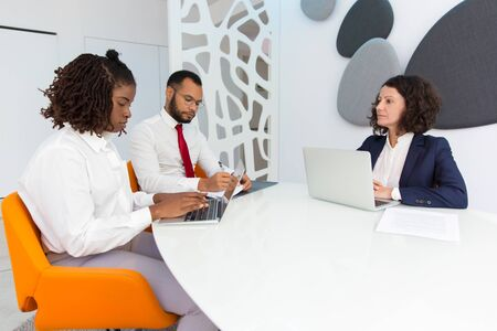 Diverse business colleagues reporting to female boss. Business man and women using laptops, checking documents and talking. Corporate meeting or leadership concept Stock Photo
