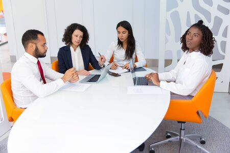 Diverse business team meeting and working on project. Business man and women sitting at conference table, using laptops, talking, writing, thinking over work issues. Teamwork concept Stock Photo