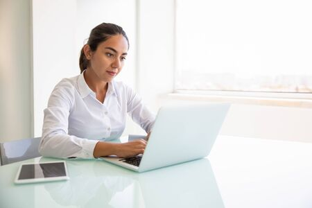 Focused female professional working on computer. Young Latin businesswoman sitting at workplace, using laptop, typing. looking at screen. Office worker concept Stock Photo