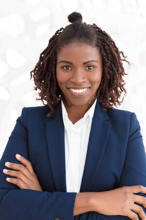 Happy young female professional posing with arms folded. Portrait of African American business woman in office suit smiling at camera. Successful business lady concept