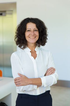 Happy successful businesswoman posing indoors. Middle aged woman in office clothing standing for camera with arms folded and smiling. Positive business woman concept