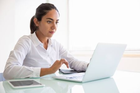 Serious focused businesswoman working on computer in office. Young Latin business woman sitting at workplace, using laptop, looking at screen. Digital communication concept Stock Photo