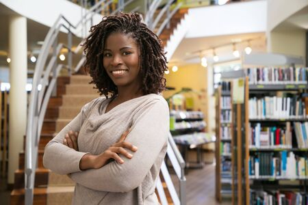 Cheerful smiling woman posing at public library. Front view of smiling lady with dreadlocks posing in front of stairs. Knowledge concept