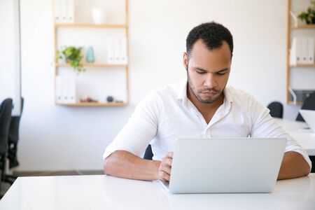 Serious male professional working on computer at workplace. Latin man in white shirt sitting at table and using laptop. Office worker concept