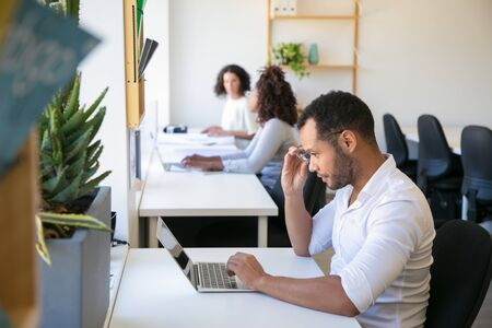 Excited male professional looking at laptop screen in surprise. Man and women in casual sitting at tables and working on computers. Team working in office concept Stockfoto