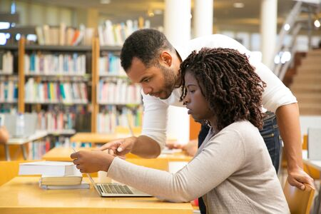 Side view of people talking and looking at laptop at library. Two students preparing to lesson. Education concept Imagens