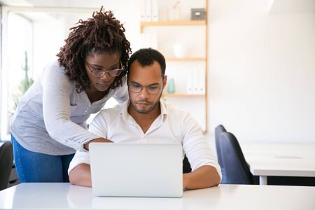 Professional helping new employee with report. Business man and woman in casual sitting and standing at workplace, using laptop, pointing at screen. Mentorship concept