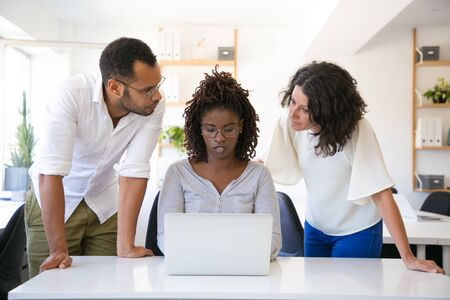 Employees consulting expert office. Business man and women in casual sitting and standing at workplace, using laptop, looking at screen, talking. Expertise concept Banco de Imagens