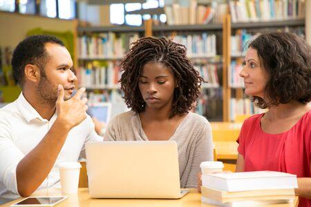 Personas reflexivas que trabajan con una computadora portátil en la biblioteca pública. Hombre afroamericano concentrado y mujer caucásica usando computadoras portátiles. Concepto de tecnología