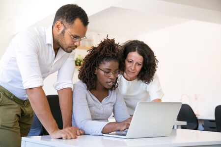 Multiethnic team collaborating on project at one workplace. Business man and women in casual sitting and standing at desk, using laptop, looking at screen and talking. Collaboration concept