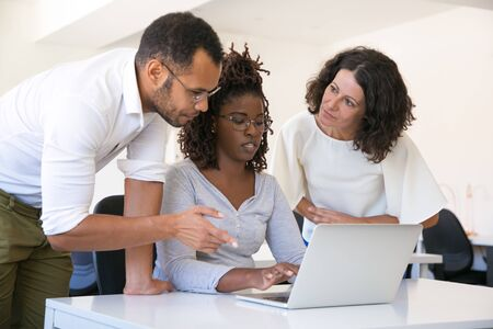 Multiethnic team discussing report on computer. Business man and women in casual sitting and standing at table, using laptop, pointing at screen and talking. Cooperation concept Banco de Imagens