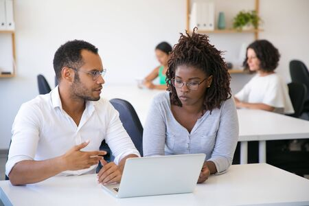 Business professional explaining project details to colleague. Man and woman sitting at table in office, using laptop, looking at screen and talking. Consulting concept