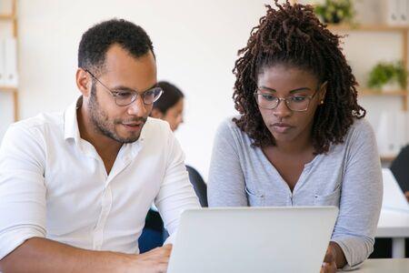 Różnorodni współpracownicy wspólnie oglądający treści na laptopie. Młody mężczyzna i kobieta przy użyciu komputera w biurze, patrząc na ekran i rozmawiając. Koncepcja dyskusji korporacyjnej Zdjęcie Seryjne