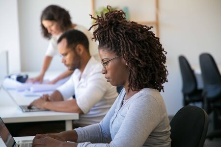 African American software company employee working at workplace. Man and women in casual sitting at table and using laptops. Software company staff concept Banco de Imagens