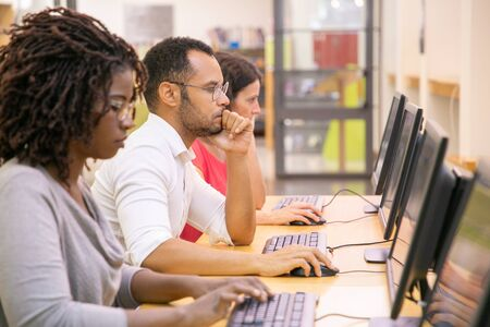 Multiracial group of students training in computer class. Line of man and women in casual sitting at table, using desktops, typing, looking at monitor. Training center concept
