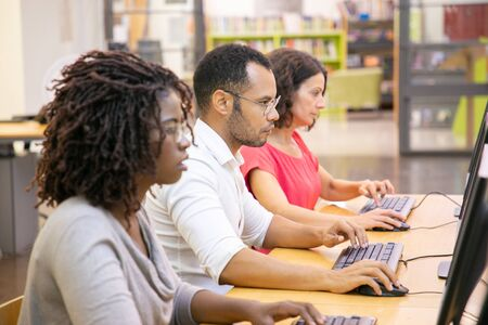 Diverse group of adult students working in computer class. Line of man and women in casual sitting at table, using desktops, typing, looking at monitor. Training center concept