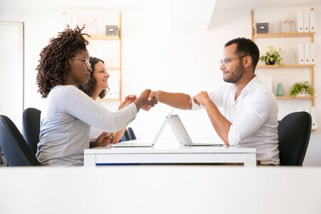 Diverse partners closing deal. Man and women in casual sitting at table and shaking hands over open laptops. Business meeting concept Stock Photo
