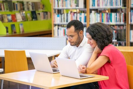 Couple of adult students doing and discussing academic research in library. Man and woman in casual sitting at desk, using laptops, talking, smiling, watching content. Leisure time in library concept