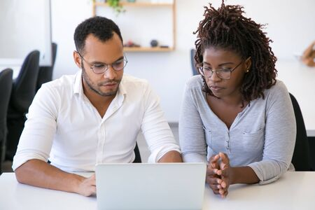 Two diverse business colleagues discussing project. Man and woman sitting at table in office, using laptop, looking at screen and talking. Business team concept