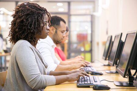 Diverse Gruppe von Mitarbeitern, die an ihren Computern arbeiten. Reihe von Männern und Frauen in zwanglosem Sitzen am Tisch, mit Desktops, Tippen, Blick auf den Monitor. Arbeitsplatzkonzept