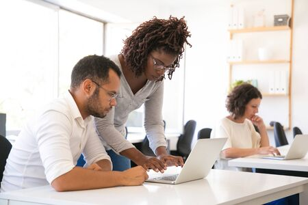 Instructor helping intern to start working laptop. Man and woman in casual sitting and standing at desk and using laptop. Internship concept