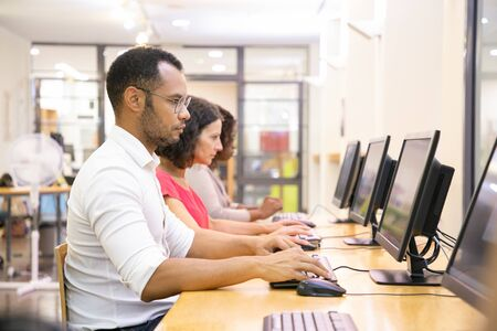 Diverse group of students taking online tests in computer class. Line of man and women in casual sitting at table, using desktops, typing, looking at monitor. Training course concept