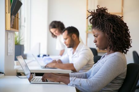 Frowning young female employee working on project in office. Man and women in casual sitting and standing at table and using laptops. Diverse staff concept