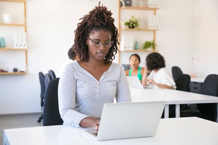Positive focused African American employee working on computer in office. Team of colleagues discussing project at meeting table in background. Teamwork concept