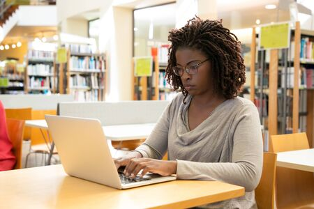 Focused female customer using free wi-fi hotspot in public library. Young African American woman sitting at desk and using laptop. Wireless technology concept