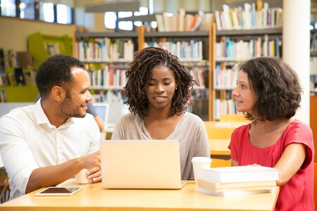 Smiling students discussing something while working with laptop. Two cheerful people sitting at library and working together. Education concept