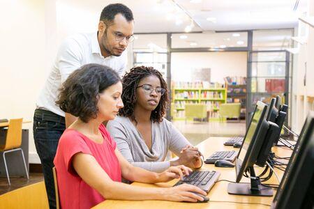 Leraar die stagiairs in computerklasse helpt. Man en vrouw zitten en staan aan een bureau, gebruiken desktop, kijken naar de monitor en praten. Trainingsconcept Stockfoto