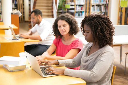 Serious students working over project at library. Two focused women using laptop while sitting at table, Education concept Imagens