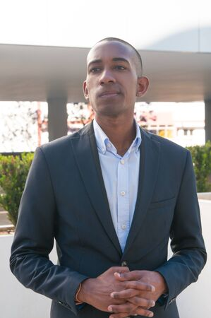 Successful young business leader waiting partners outside. African American businessman standing near office building and looking into distance. Confident business man concept