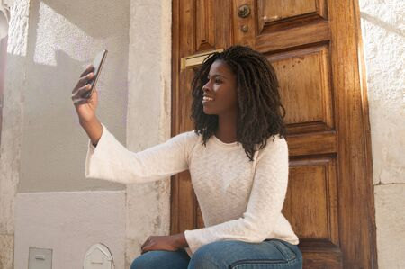 Cheerful young woman taking selfie outside. Young black woman sitting near building entrance and posing for smartphone camera. Selfie concept