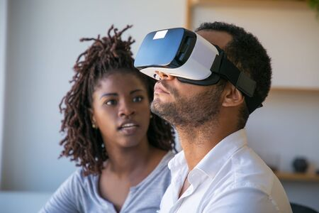 Diverse developers testing VR product. Young woman talking to male colleague wearing virtual reality glasses. Software test concept