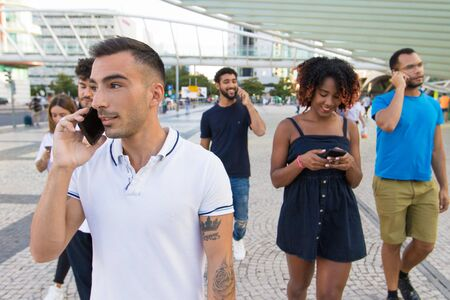 Diverse group of people excited with their smartphones. Mix raced men and women walking outside, talking on cells, using mobile phones. Mobile communication concept